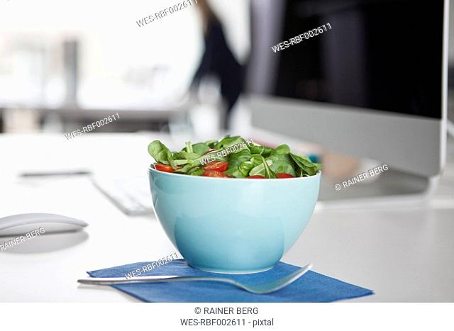 Bowl with garnished salad on a desk in an office