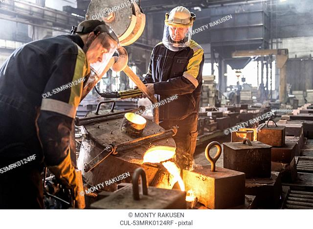Workers pouring molten metal in foundry