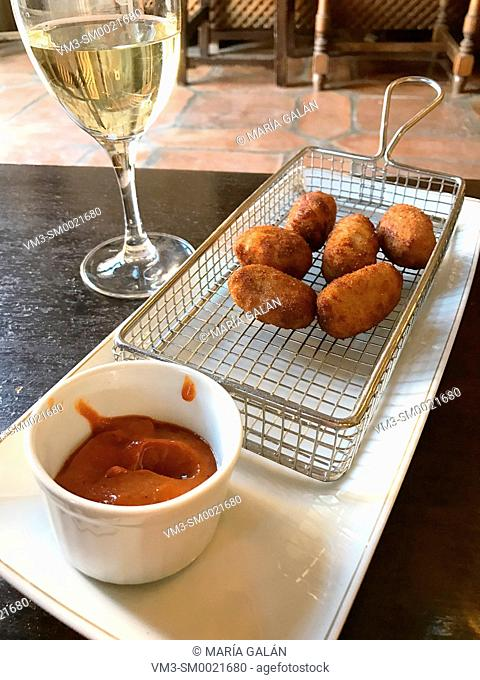 Croquettes with tomato sauce and glass of white wine. Spain