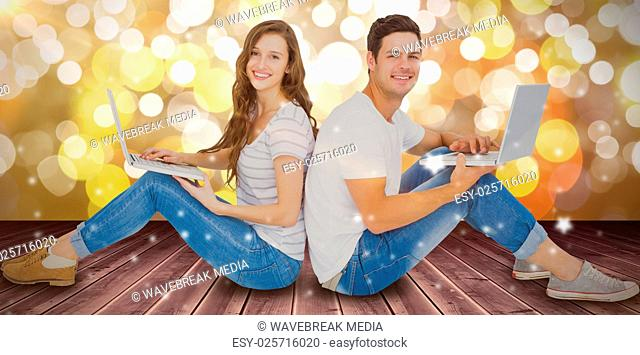 Composite image of couple sitting on floor back to back using laptop