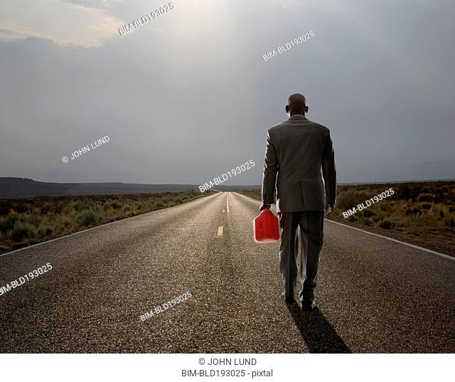 African American businessman carrying gas can on remote highway