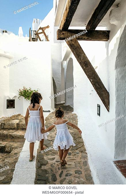 Spain, Balearic Islands, Menorca, Binibeca, back view of two little sisters walking hand in hand