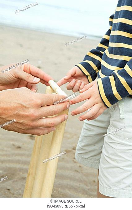 Adult and child setting up crickets stumps