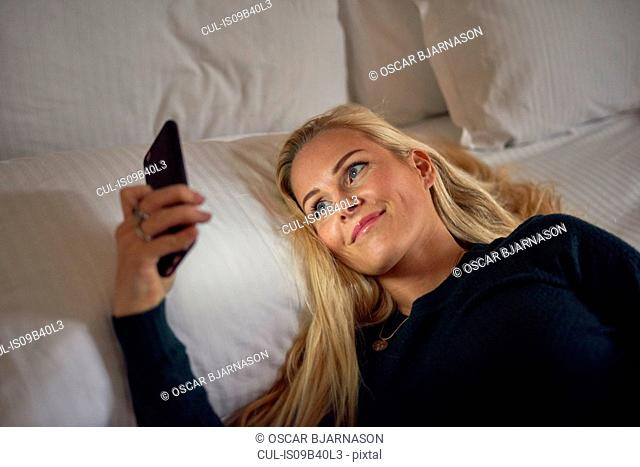 Mid adult woman lying on bed, using smartphone, smiling