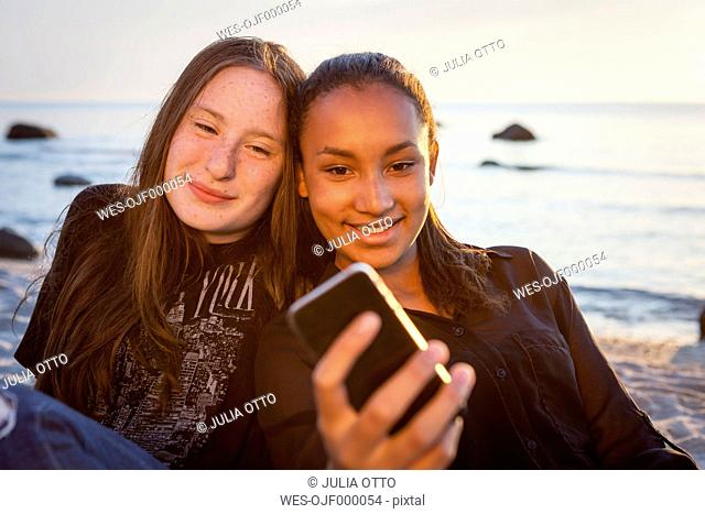 Germany, Ruegen, Two young female friends with smartphone at the beach