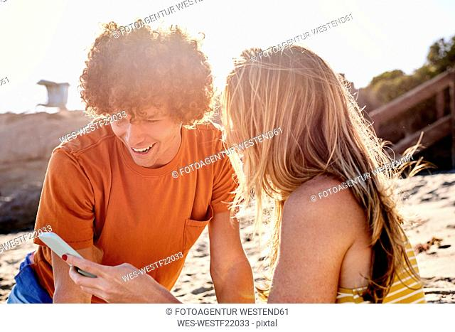 Couple checking cell phone on the beach
