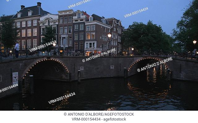 A tourist boat at the bridge of 15 bridges. Amsterdam. Netherlands