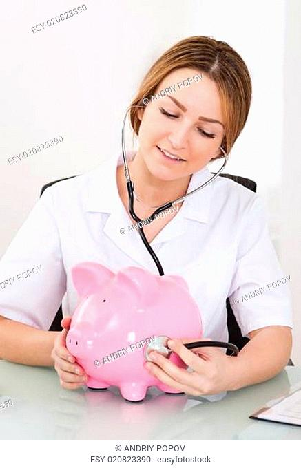 Female Doctor Examining Piggybank