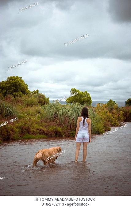 a woman and her dog (golden retriever) walking thru the wet path