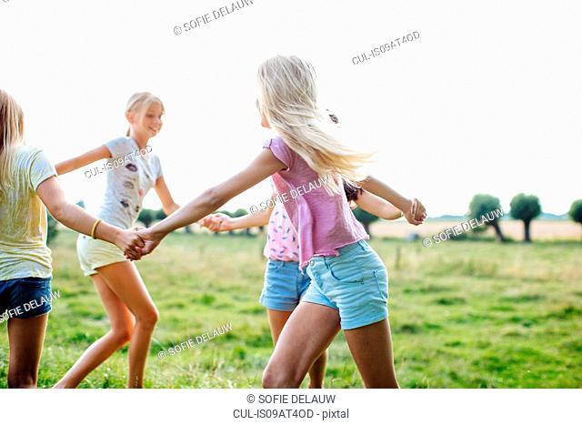 Girls dancing in ring on field, Flanders, Belgium