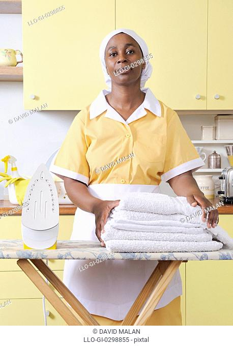 Domestic worker with ironing board, iron and white sheets, Cape Town, Western Cape Province, South Africa