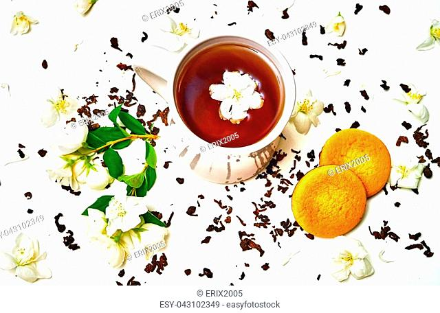 Tea cup with dried leaves and fragrant Jasmine flowers and cookie on white background. Top view