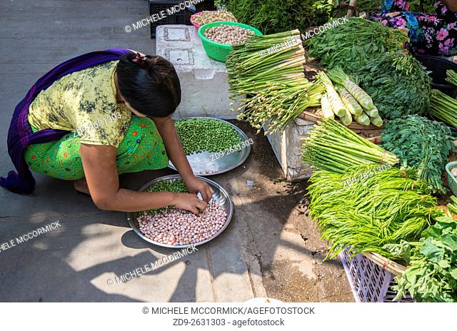 woman prepares her vegetables for sale on a street in Yangon