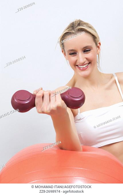 Healthy woman exercising with weights