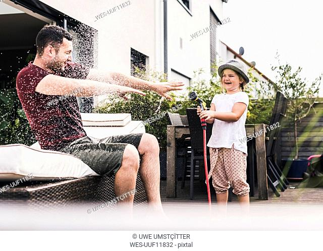 Fathercand daughter in the garden, daughter splashing water with hose