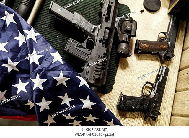 Rifles, guns and American flag on table