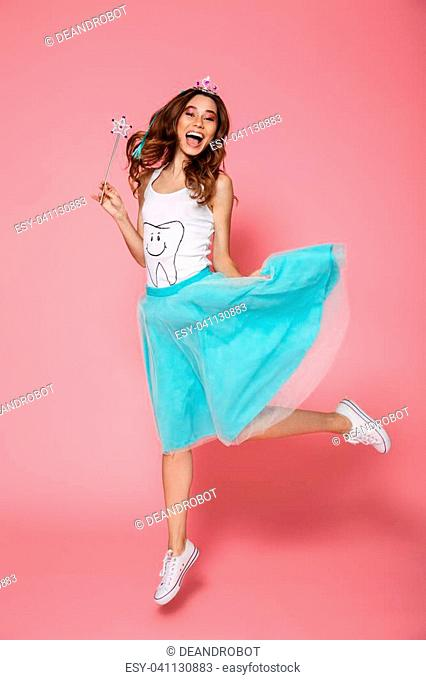 Full length photo of charming brunette woman dressed like tooth fairy holding magic wand, looking at camera while jumping over pink background