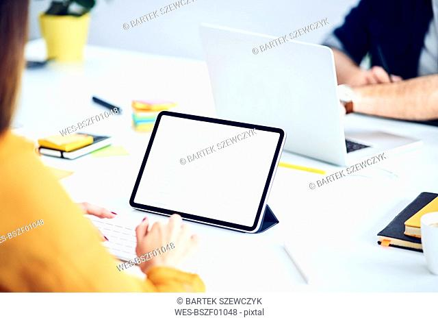 Close-up of businesswoman using tablet at desk in office