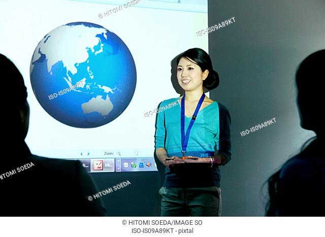 Woman doing presentation with globe projected on wall