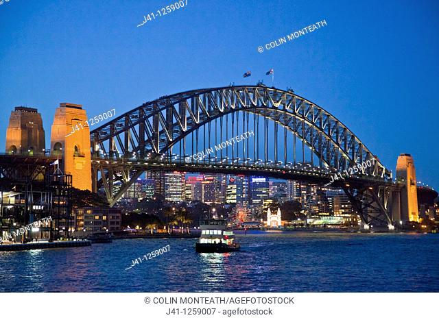 Sydney harbour bridge with ferry approaching Circular Quay, dusk, Sydney, NSW, Australia