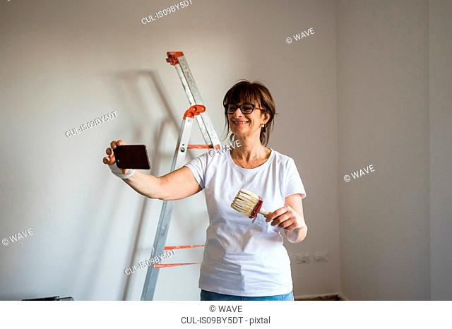 Senior woman taking smartphone selfie holding paint brush in house interior