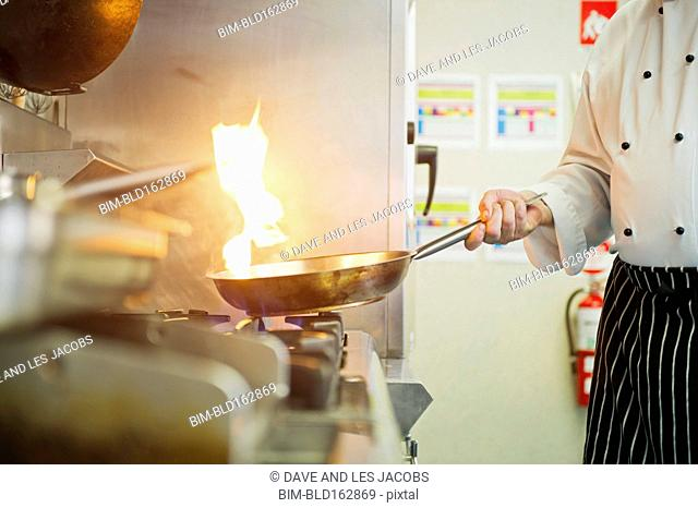 Caucasian chef cooking in restaurant kitchen