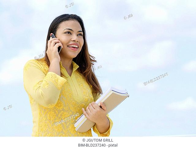 Hispanic woman holding notebooks talking on cell phone