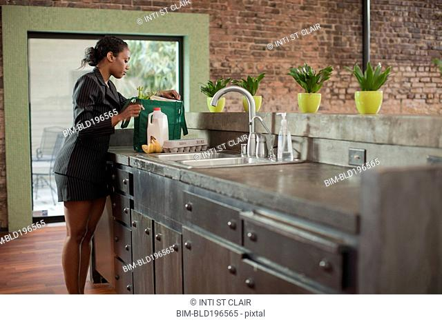 Mixed race woman unloading groceries in kitchen