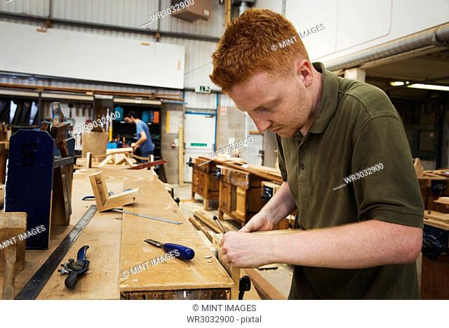 Man working a boat-builder's workshop, joining together two pieces of wood
