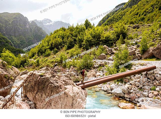 Man crossing waal river on bridge made of pipes, Accursed mountains, Theth, Shkoder, Albania, Europe
