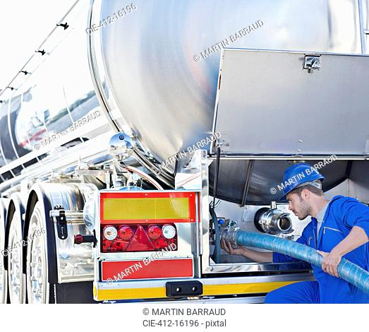 Worker attaching hose to back of stainless steel milk tanker