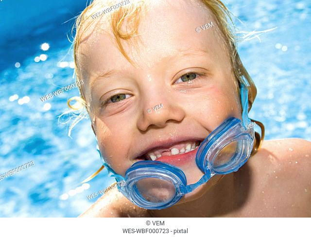 Germany, boy with swimming goggle, portrait, smiling