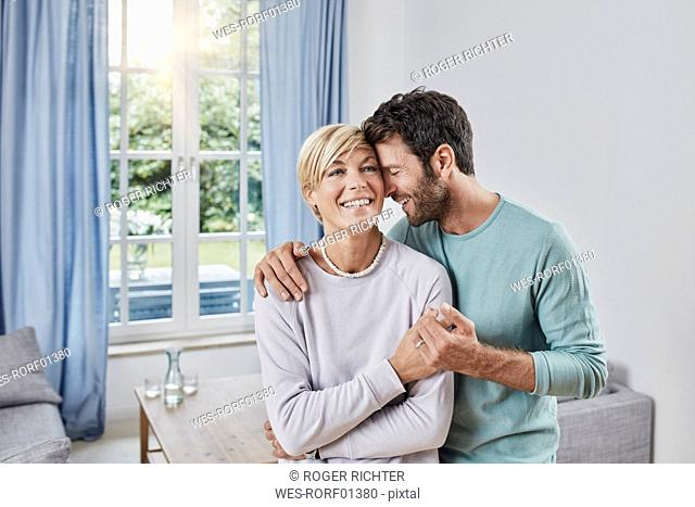 Happy affectionate couple embracing at home