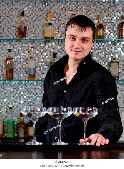 Smiling barman serving a batch of martini cocktails standing behind the bar counter smiling at the camera with the cocktails lined up in front of him