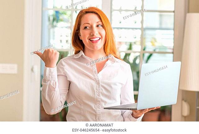 Redhead woman using computer laptop at home pointing with hand and finger up with happy face smiling