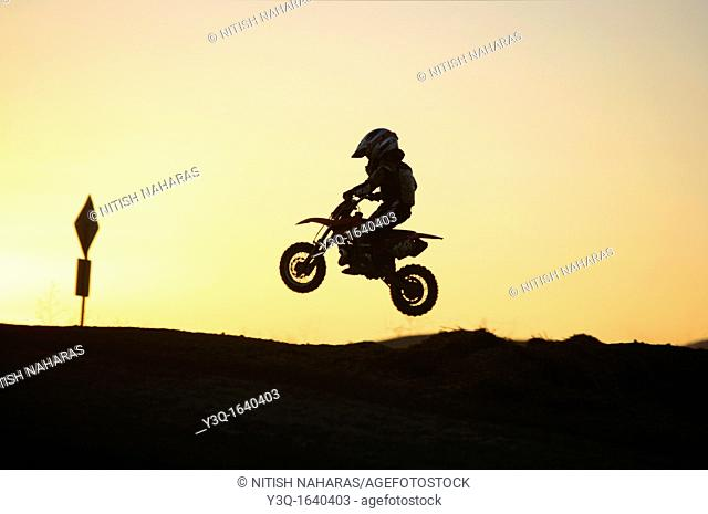 Young child learning the ropes of motocross riding in California, USA