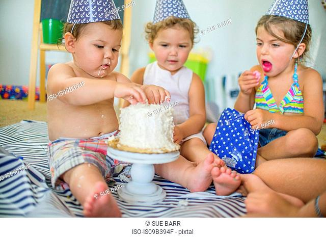 Siblings looking at boy poking fingers into birthday cake