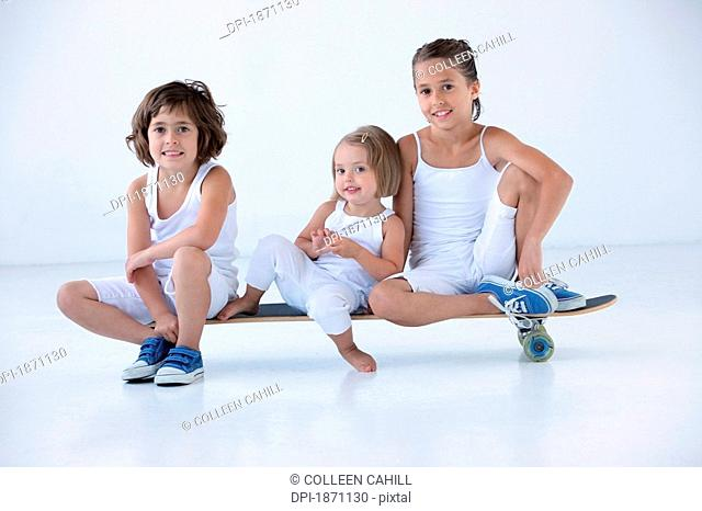 three young girls sitting on a longboard