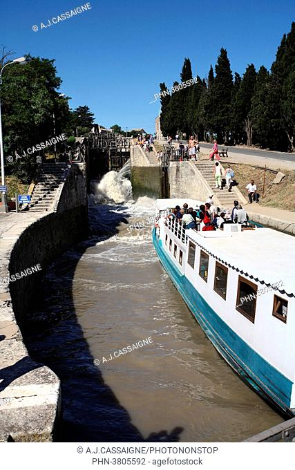 France, Southern France, Canal du Midi. Fonseranes Lock near Beziers, with a touristic boat going throug the round lock. White and blue boat