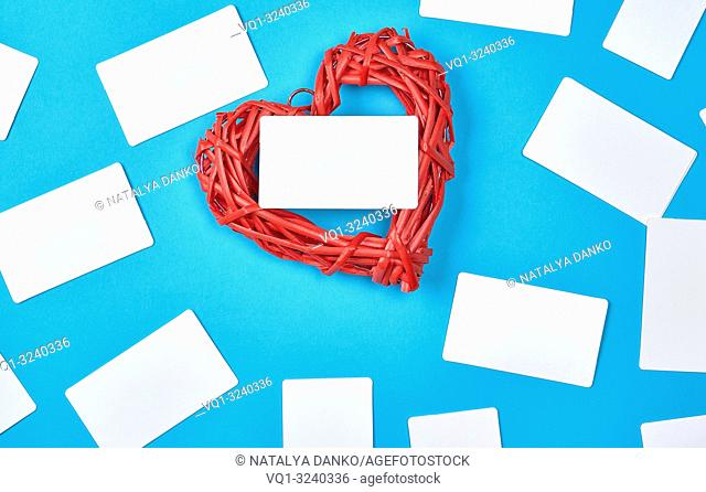 wooden wicker red heart and empty white paper business cards on blue background