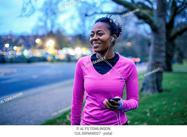 Young woman in exercise clothes, wearing earphones