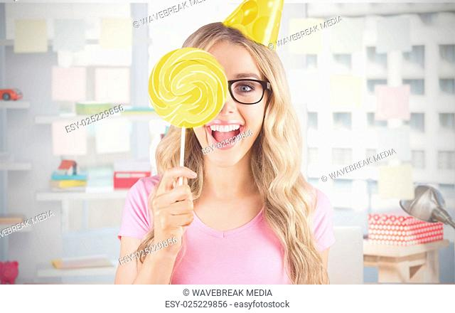 Composite image of portrait of a hipster hiding herself behind a lollipop