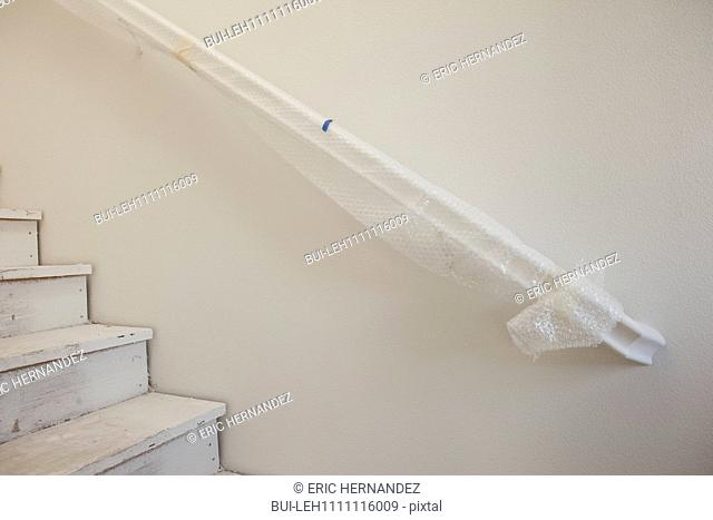 Close-up of white stairs with handrail at home