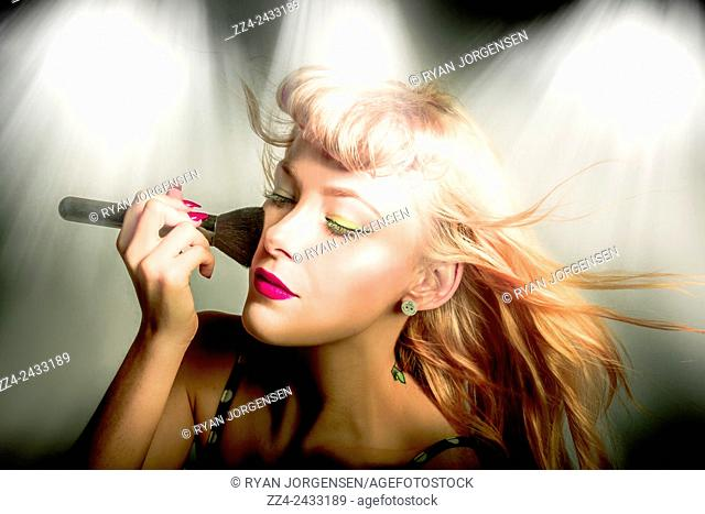 Closeup dramatic portrait of a gorgeous pinup woman with wind blown long blond hair style applying dry tonal foundation cosmetic to face using makeup blusher