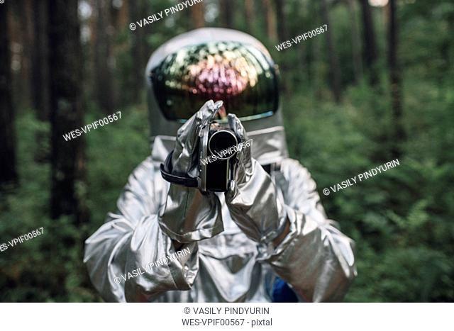 Spaceman exploring nature, filming trees