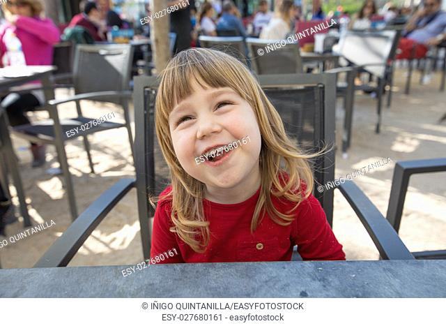 portrait of blonde three years old child face, with red shirt, funny laughing eating cheese snacks, with crumbs in mouth