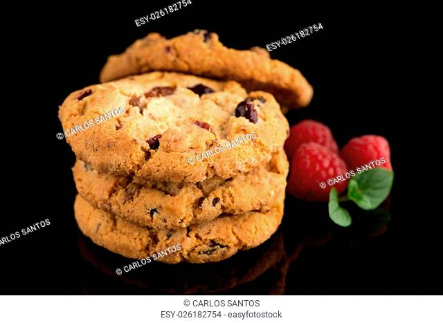 Dried fruits chip cookies and raspberries isolated on black background