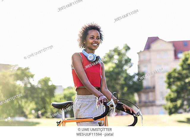 Smiling sporty young woman with bicycle in park