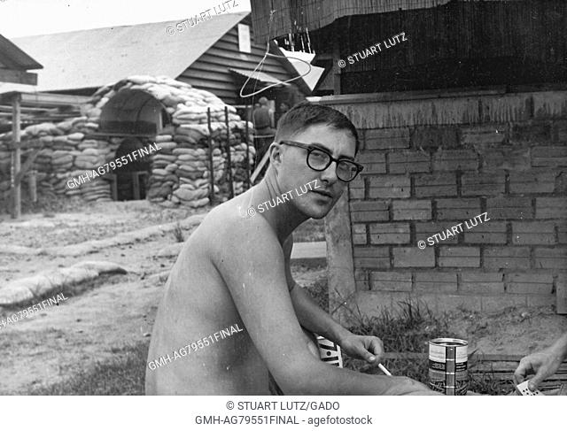A shirtless United States Army soldier smoking a cigarette and playing cards, the hand of his opponent can be seen at the right side of the image