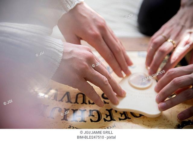Hands of Caucasian women using a Ouija board